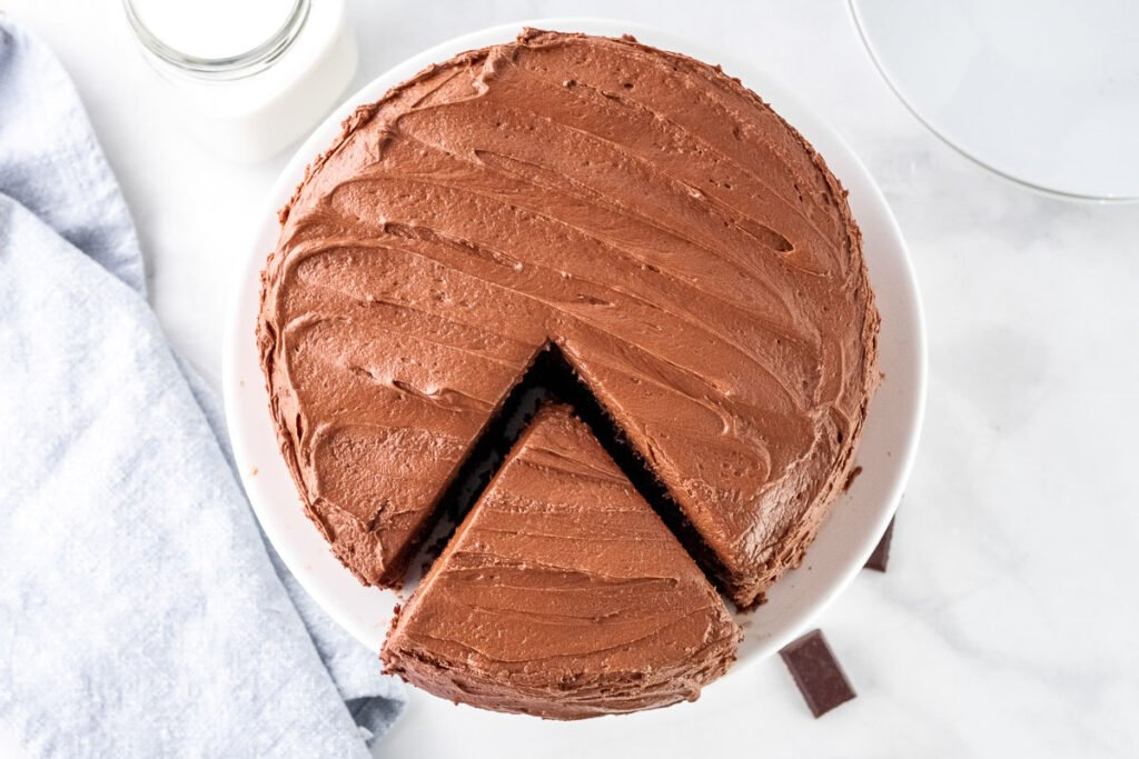 a chocolate frosted cake on a white cake stand with a triangle piece cut out but still on the stand