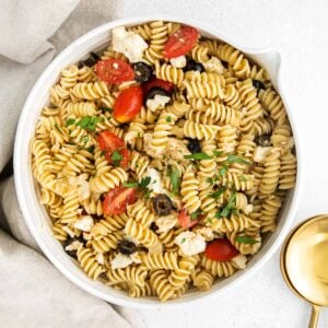 closeup of greek pasta salad with rotini pasta, feta cheese, olives and tomatoes