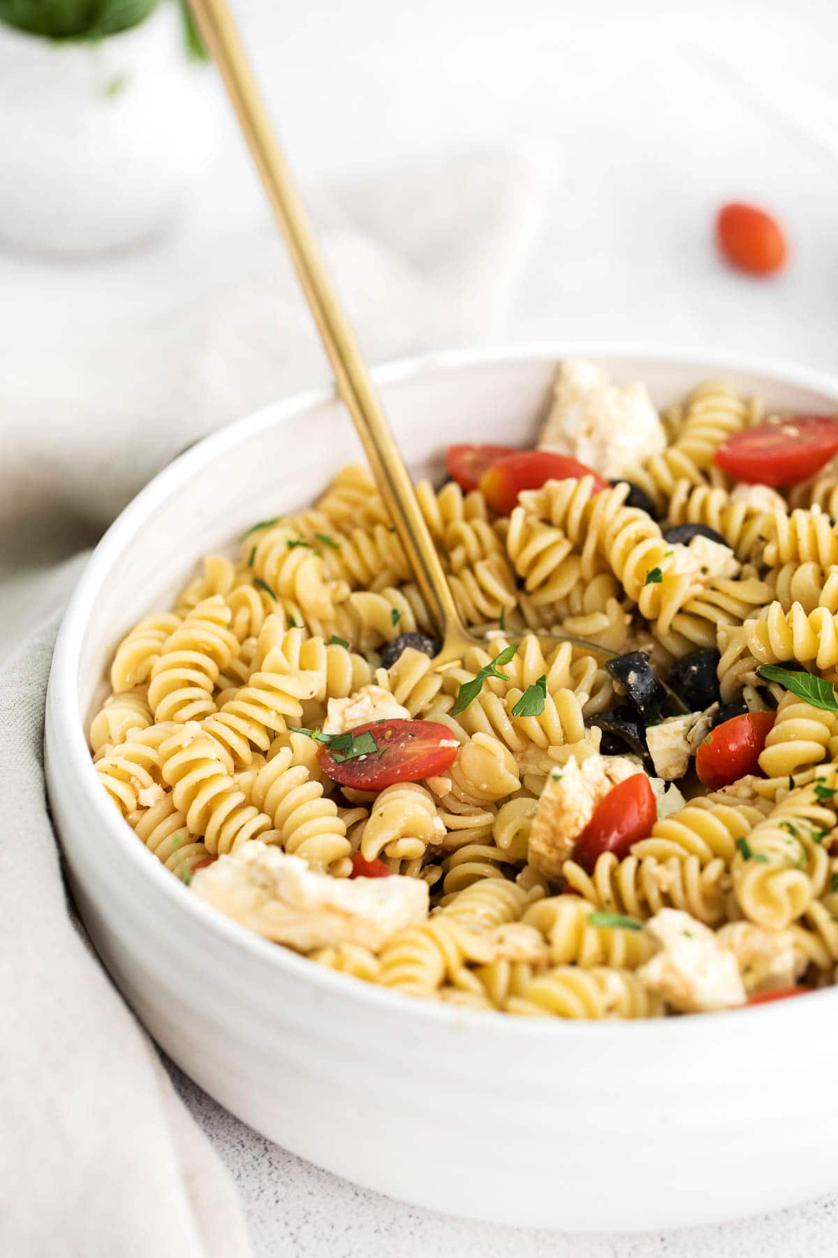closeup of greek pasta salad mixed with cherry tomatoes, olives and feta cheese in a white serving bowl