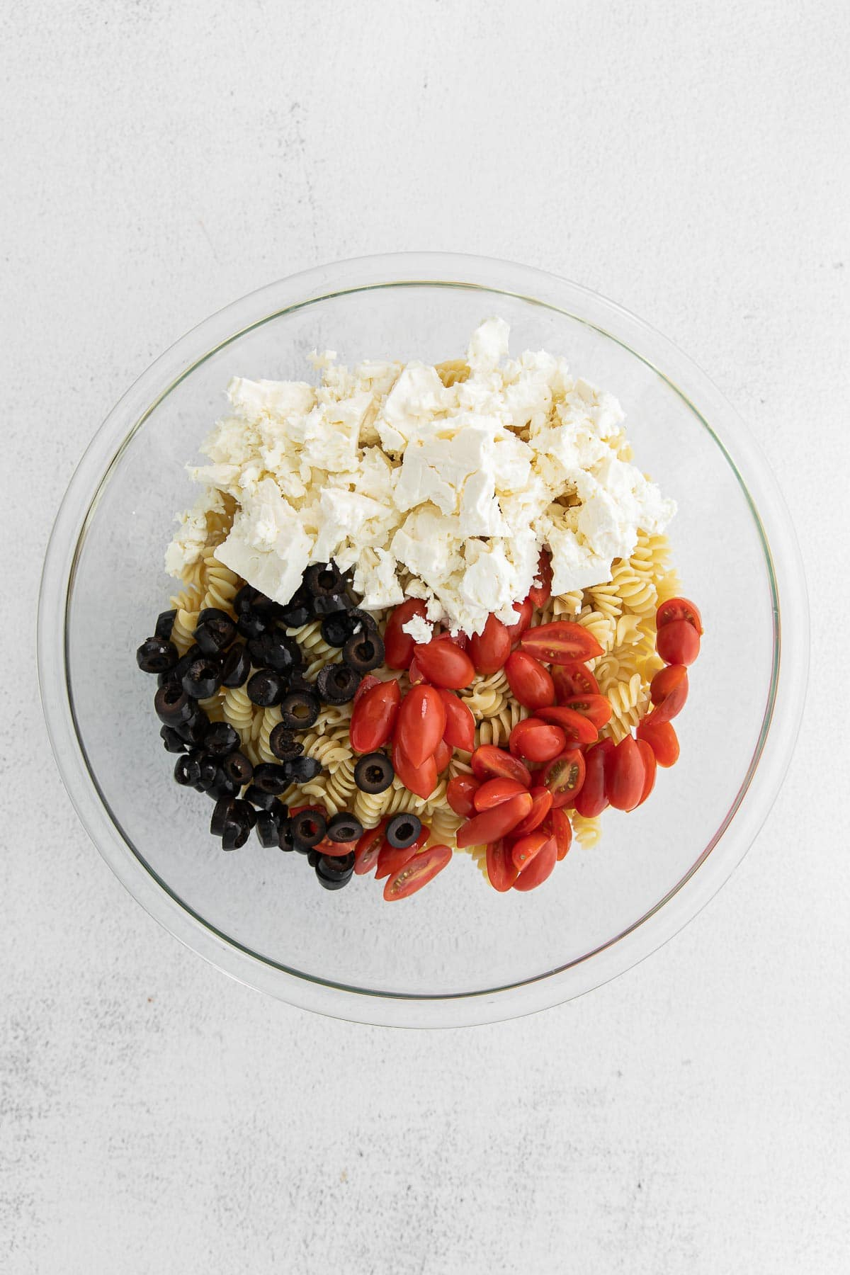 glass bowl with rotini pasta topped with sections of sliced cherry tomatoes, sliced olives and chunks of feta