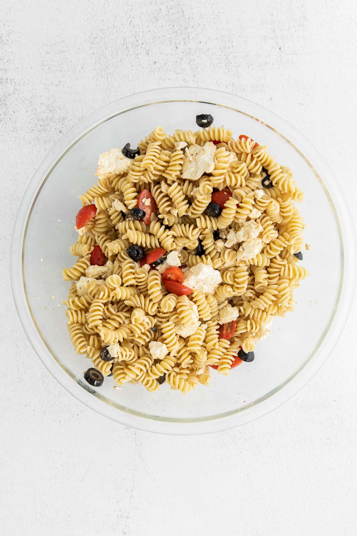 greek pasta salad mixed in a big glass bowl