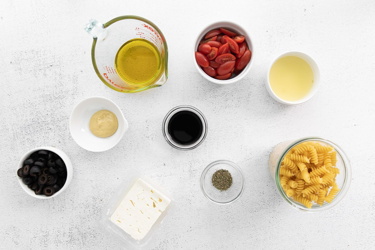 several ingredients in bowls for greek pasta salad - sliced olives, cherry tomatoes, uncooked rotini pasta, oregano, block of feta cheese, dijon mustard, olive oil and lemon juice