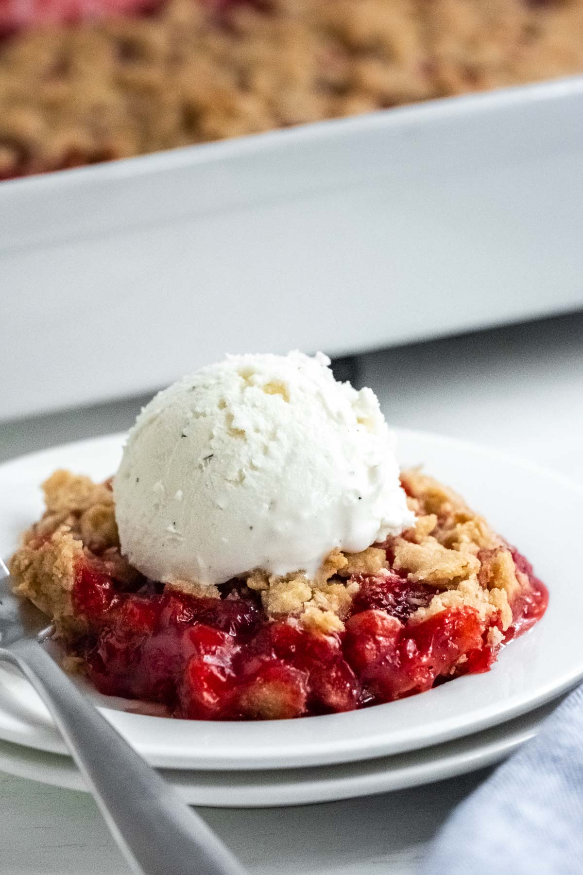 closeup of strawberry crumble topped with ice cream on a white plate with baking dish in the background
