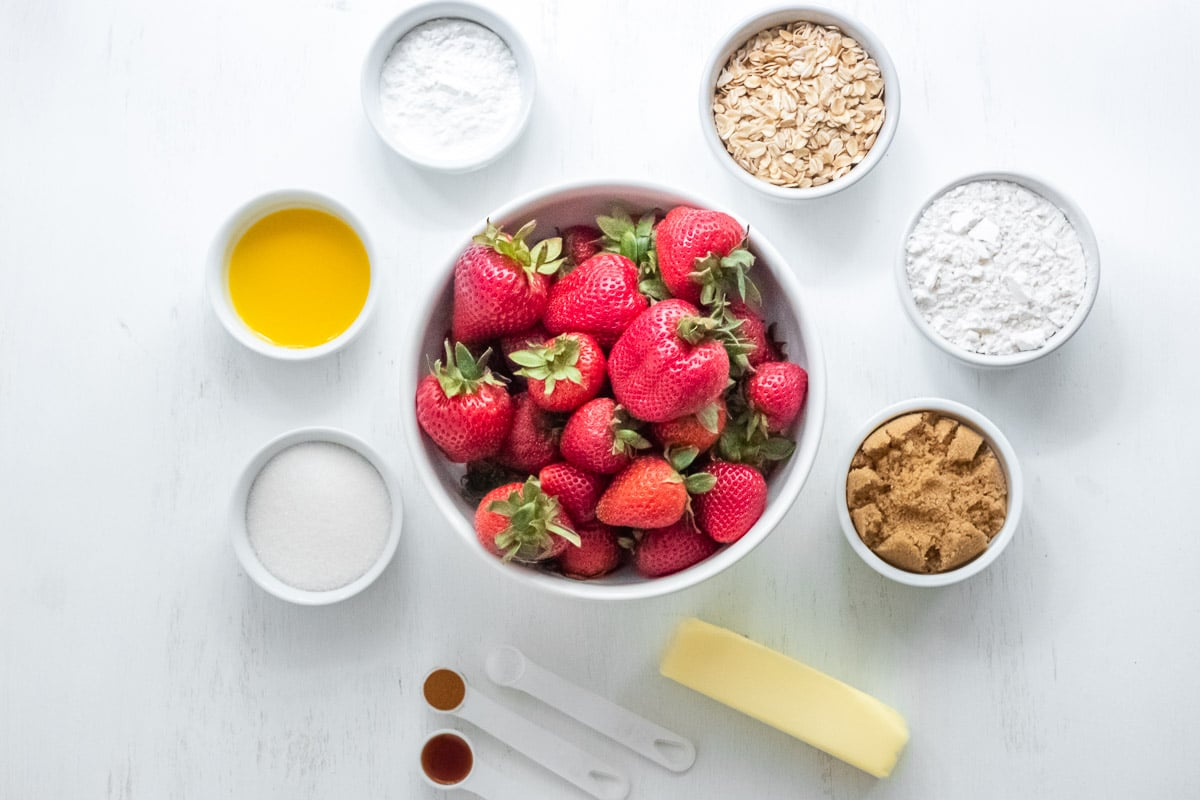 white bowls filled with ingredient for strawberry crumble: fresh strawberries, brown sugar, oats, flour, butter, sugar