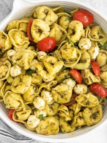 white bowl with tortellini pasta salad with tomatoes and pesto sauce