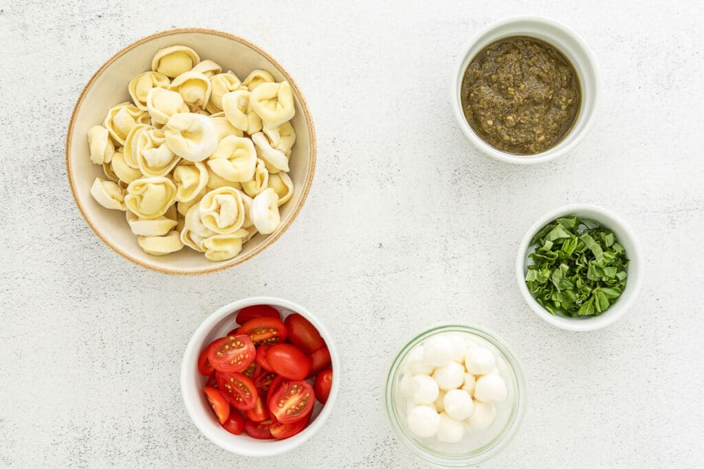 small bowls of tortellini pasta, pesto, cherry tomatoes, mozzarella cheese balls, and fresh basil
