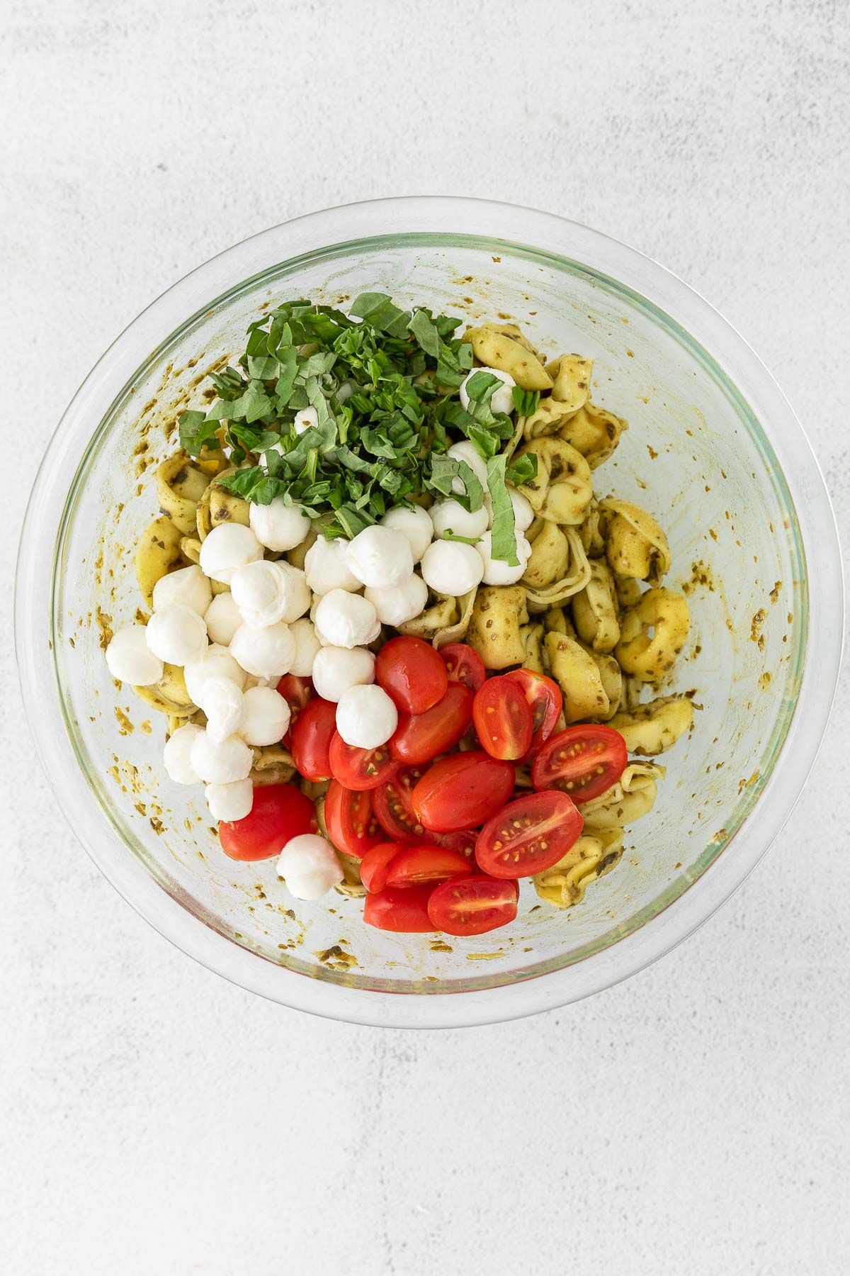 tortellini in a glass bowl with tomatoes, mozzarella cheese and fresh basil