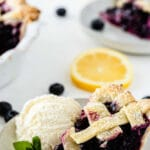 slice of blueberry pie on a white plate with a scoop of vanilla ice cream