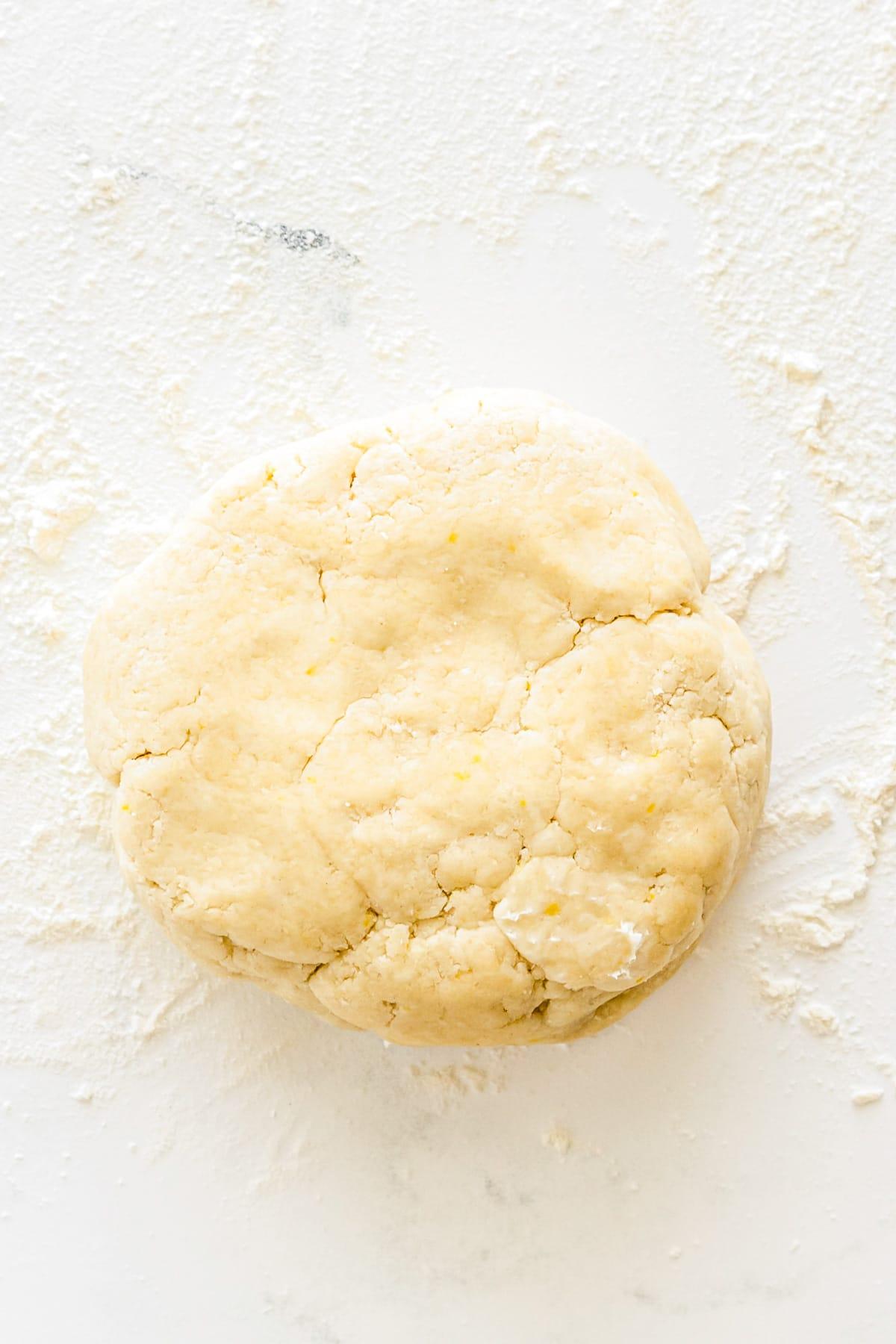 pie crust dough ball on a floured counter surface