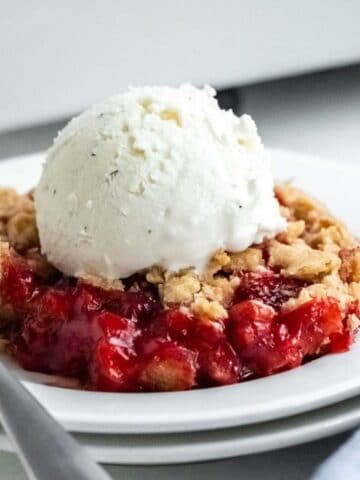 closeup of strawberry crumble with a scoop of vanilla ice cream