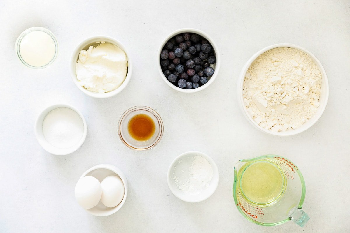 several white bowls with flour, sugar, oil, vanilla, eggs, and fresh blueberries