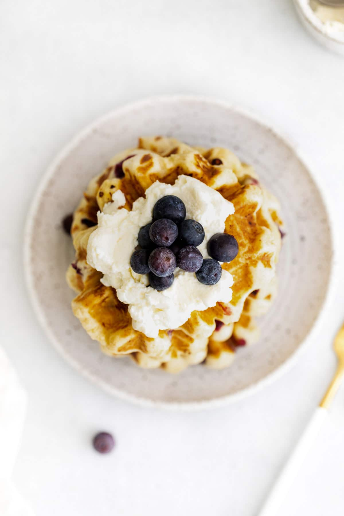 a white plate with blueberry waffles