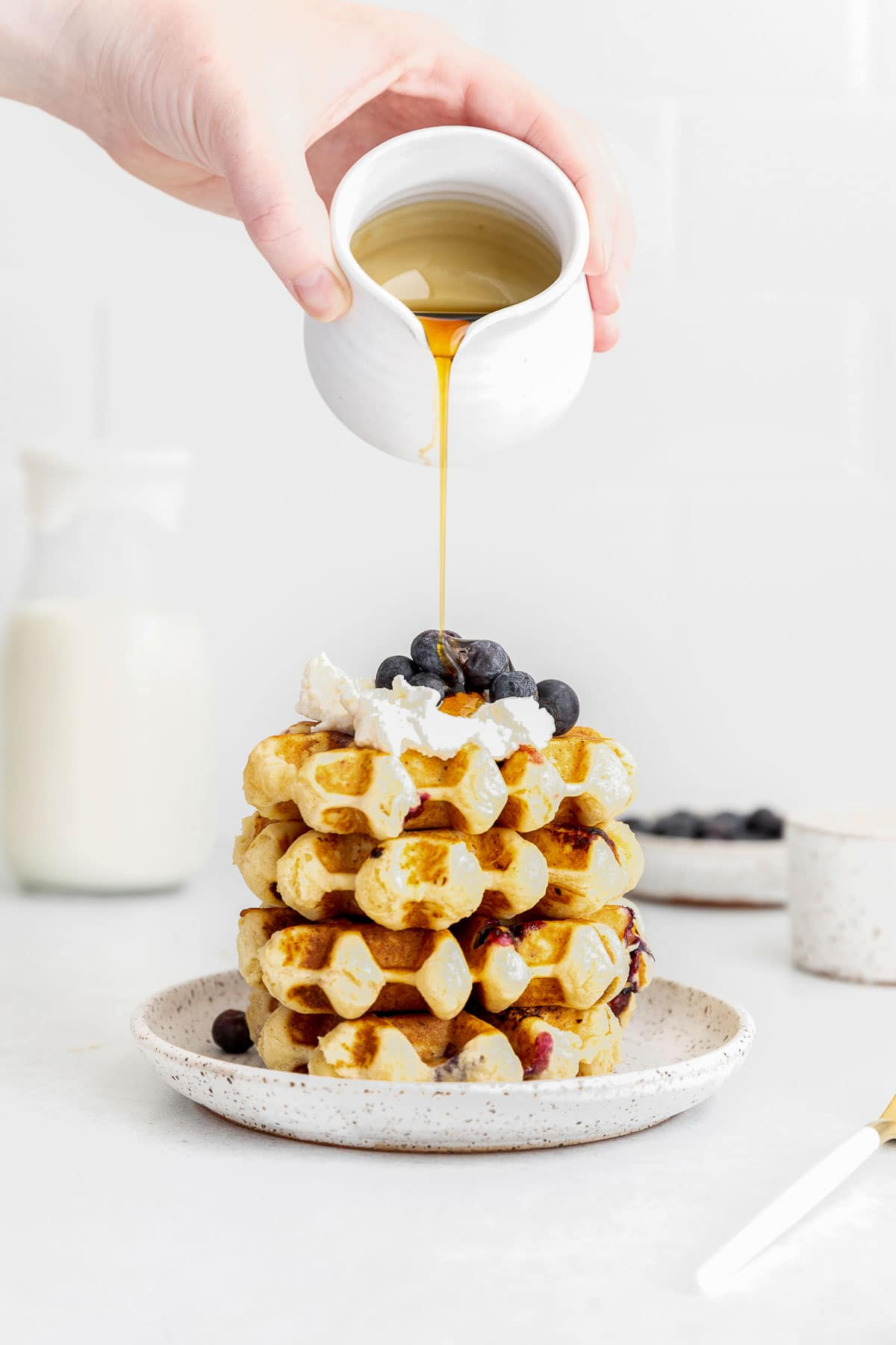 maple syrup being poured over a stack of blueberry waffles