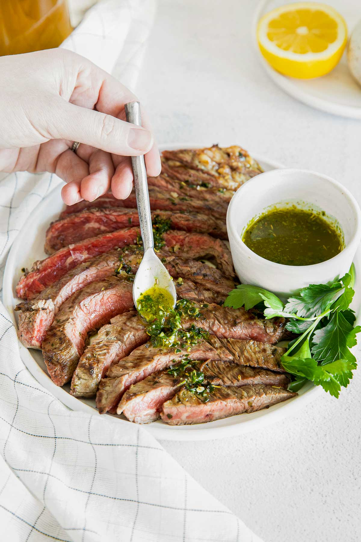 white plate with a medium rare sliced flank steak with chimichurri sauce being drizzled over and a bowl of sauce next to it