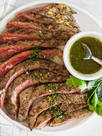 sliced flank steak with a small bowl of chimichurri sauce on the side on a white plate