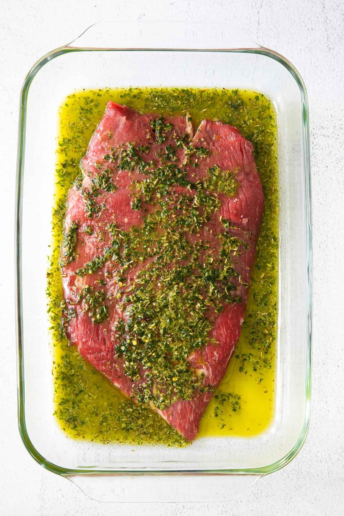 glass dish with raw flank steak marinading in green chimichurri sauce