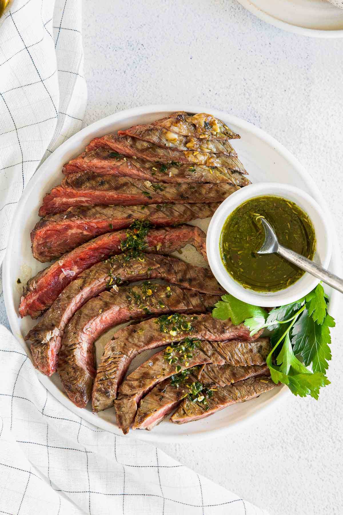 white plate with a medium rare sliced flank steak topped with a drizzle of chimichurri sauce.