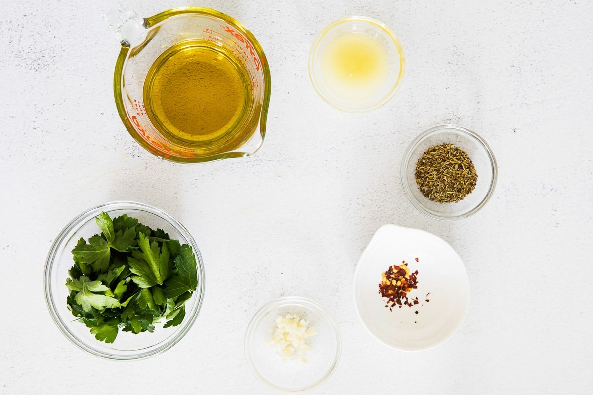 several glass bowls with fresh parsley, minced garlic, crushed red pepper, oil and oregano
