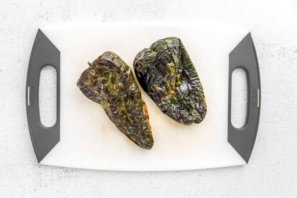 two roasted poblano peppers on a white cutting board