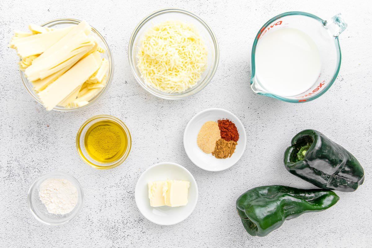 several bowls filled with ingredients for poblano queso - american cheese, mozzarella cheese, flour, olive oil, peppers, and spices