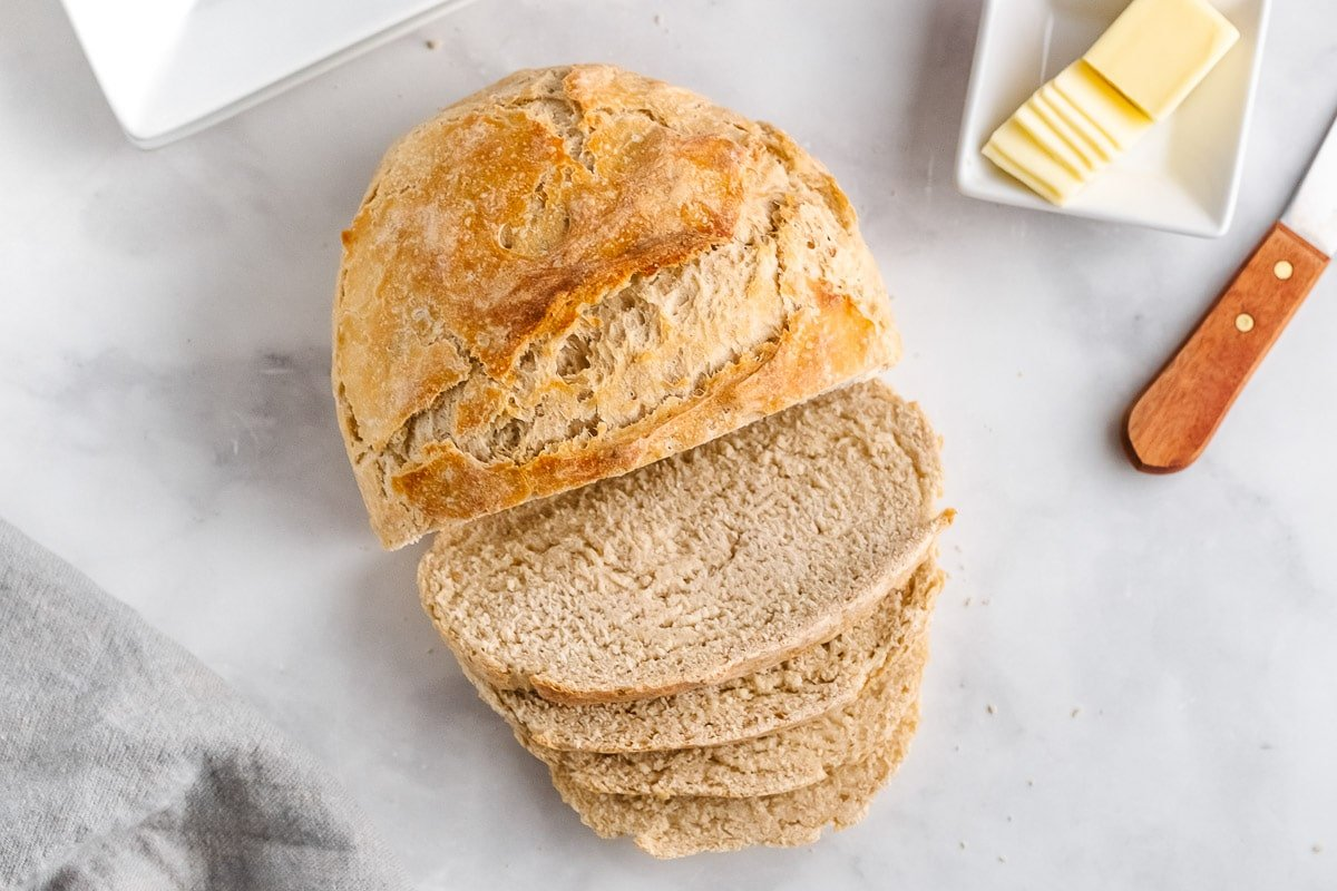 round loaf of bread with four slices cut with butter dish on the side