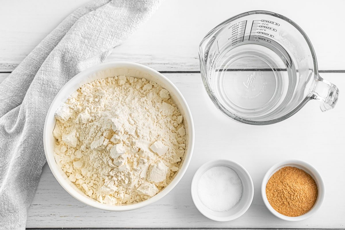 several glass bowls filled with ingredients - flour, yeast, salt and water
