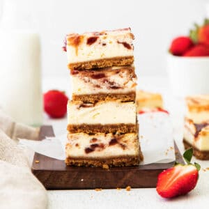 closeup of a stack of four strawberry cheesecake bars on a wood cutting board and white parchment paper