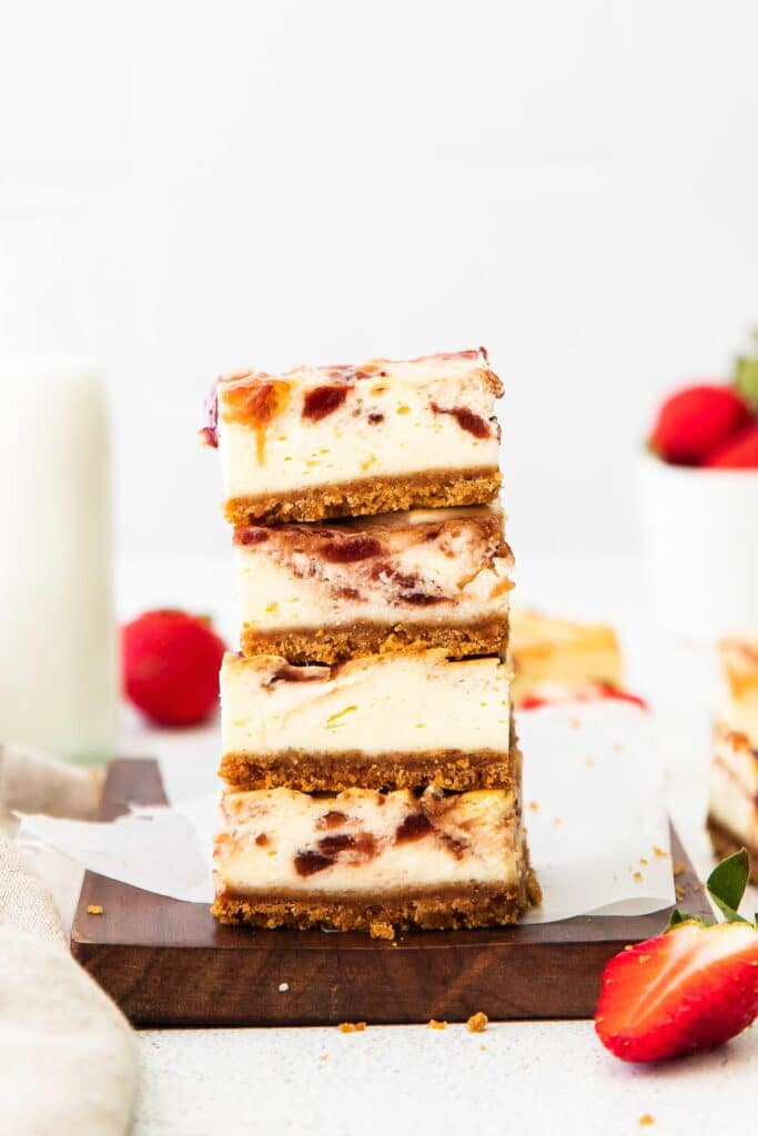 closeup of a stack of four strawberry cheesecake bars on a wood cutting board with fresh strawberries