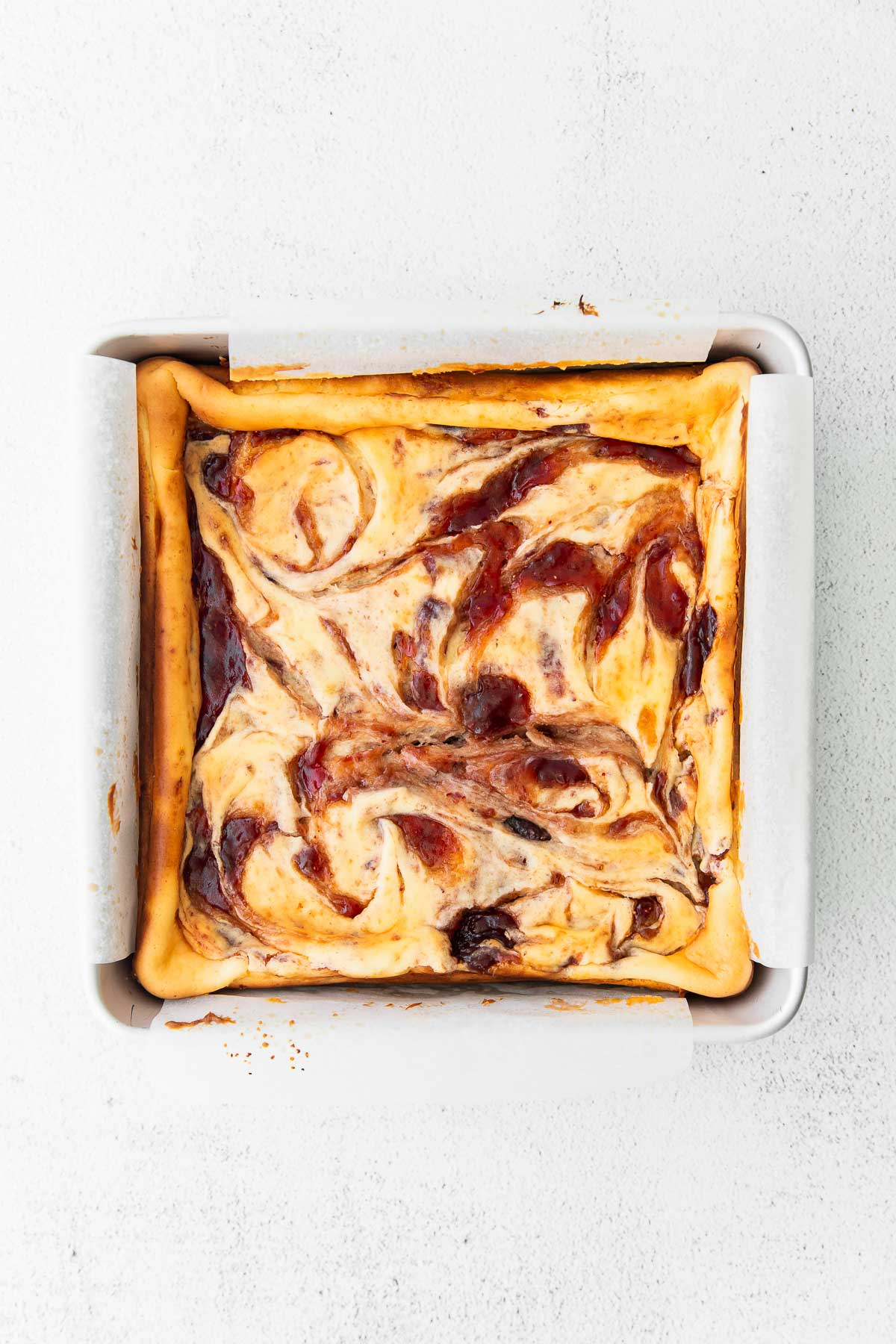 strawberry swirled cheesecake bars baked in a square baking dish