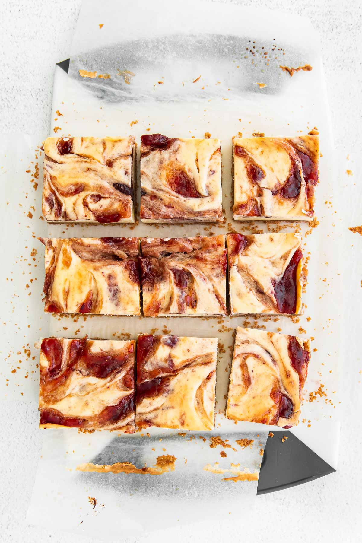 nine strawberry cheesecake bars cut on parchment paper