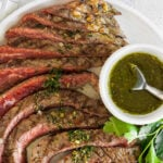 sliced steak with chimichurri sauce drizzled on top