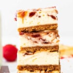 closeup of a stack of four strawberry cheesecake bars on a wood cutting board with text overlay that reads Strawberry Cheesecake Bars