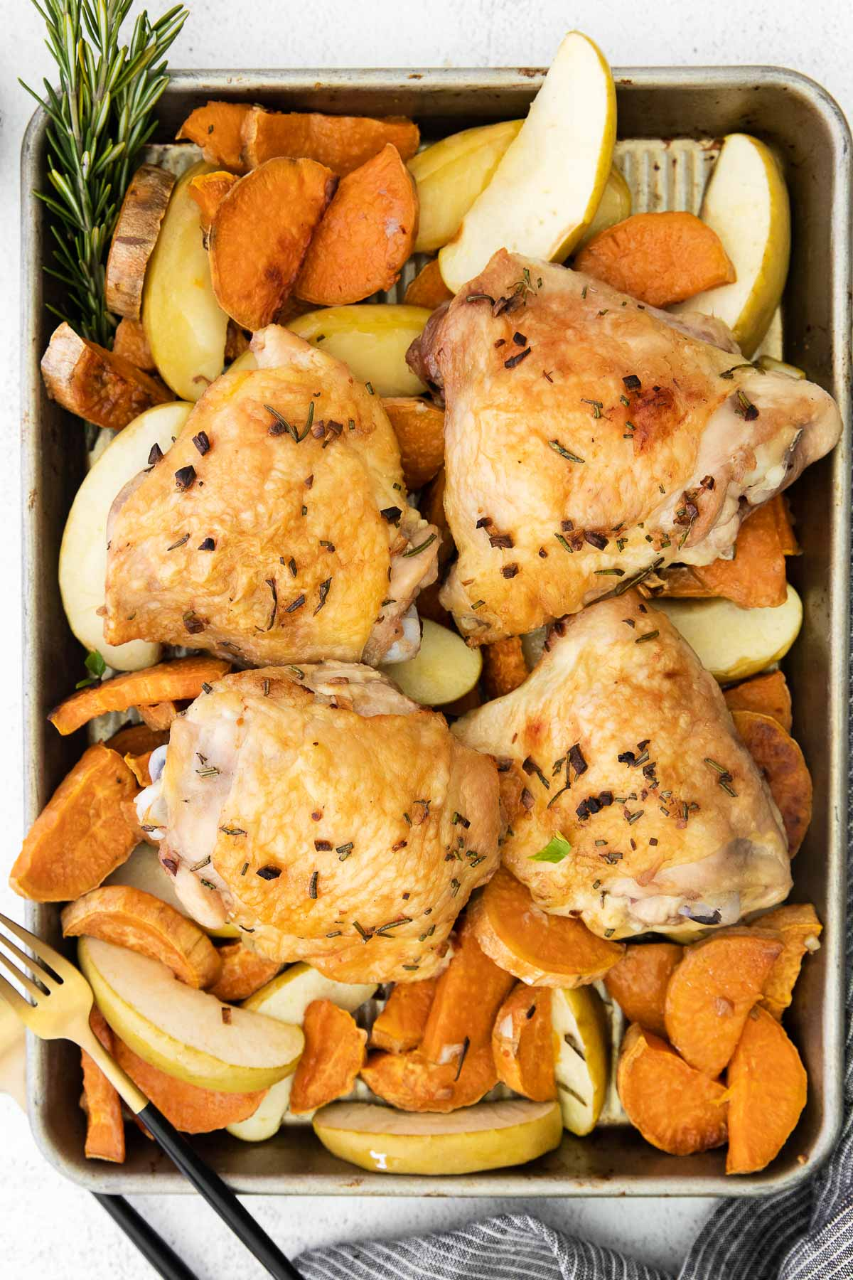 sweet potatoes, apples and chicken thighs on a silver sheet pan with a fork