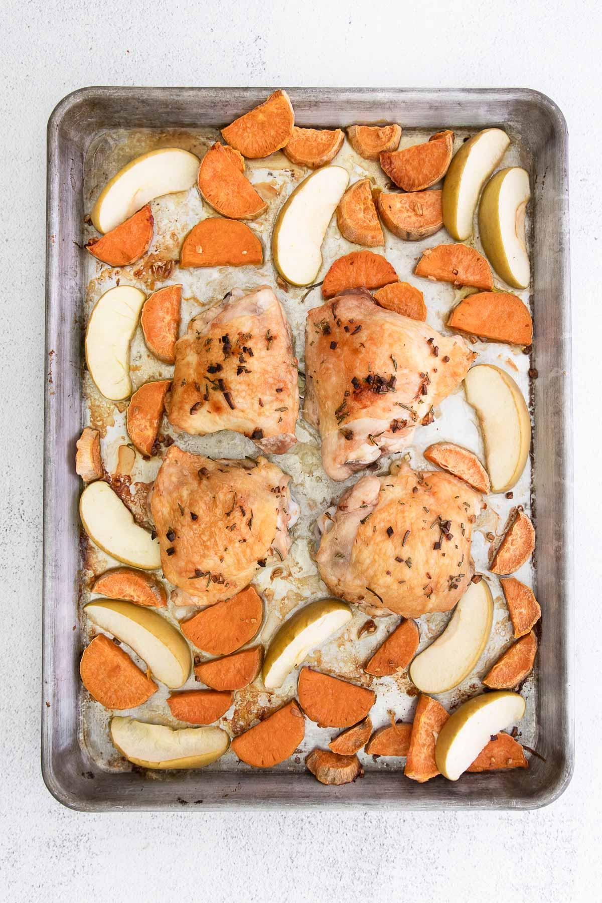 sheet pan with cooked chicken thighs, sweet potatoes and apples