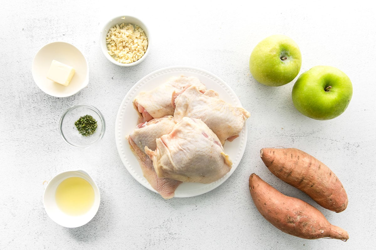 raw chicken breasts, two sweet potatoes, green apples, with small bowls of olive oil, rosemary, butter and garlic
