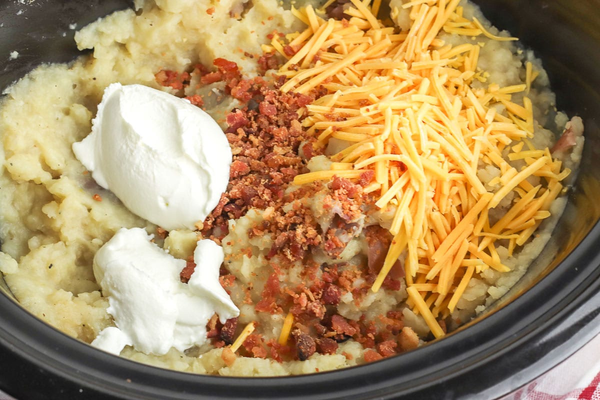 slow cooker with mashed potatoes, a dollop of sour cream, shredded cheese, and bacon pieces