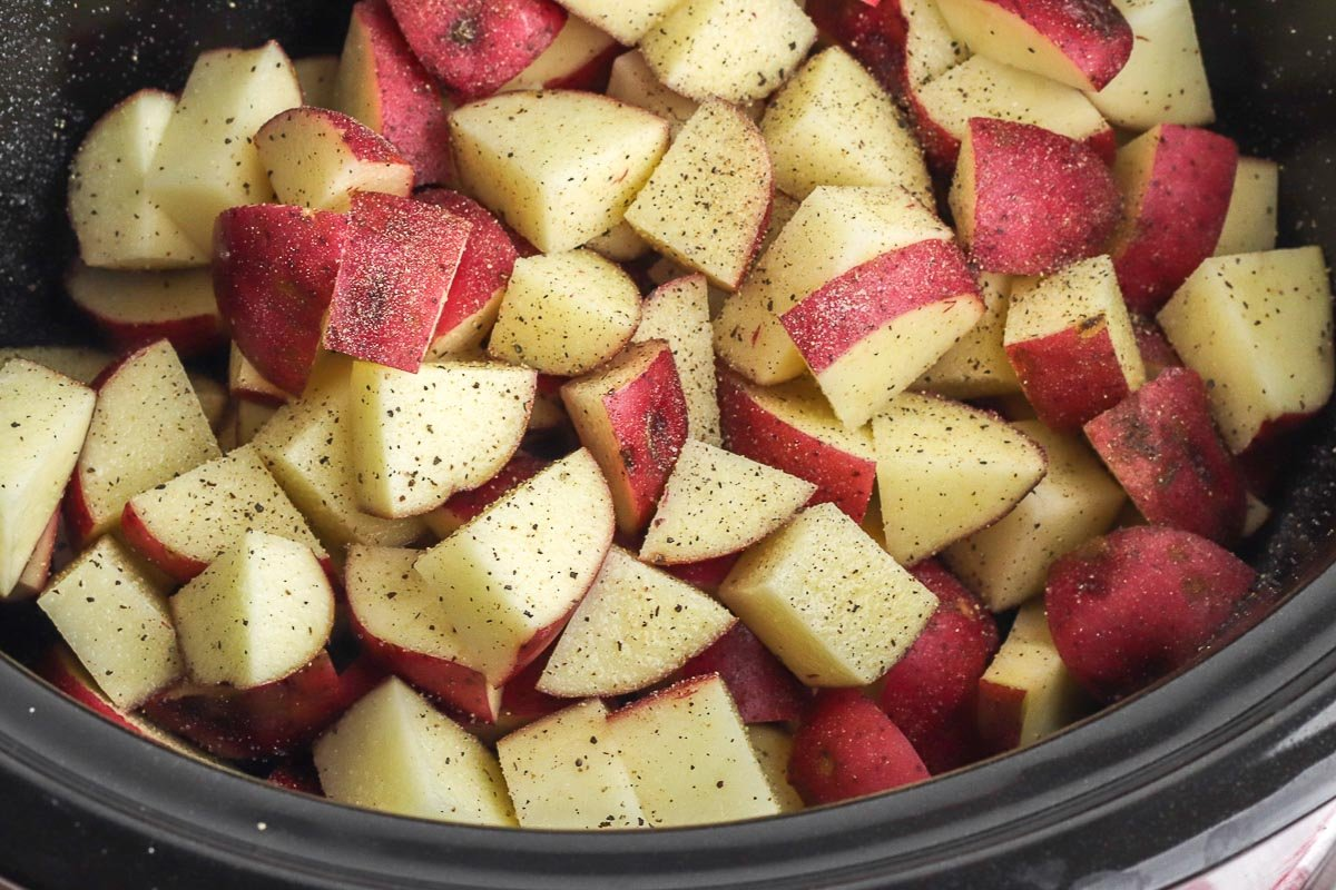 cubes of red potatoes in a black slow cooker