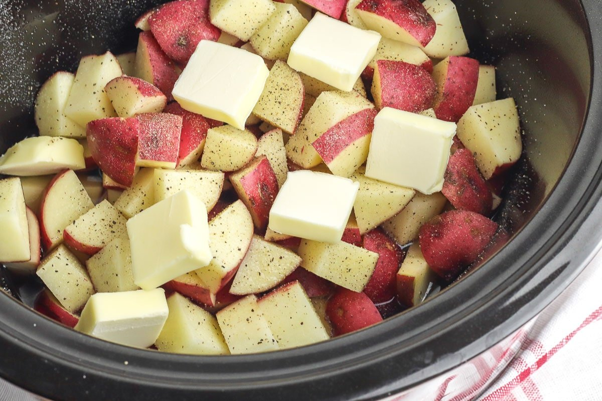diced red potatoes in a slow cooker with butter slices on top