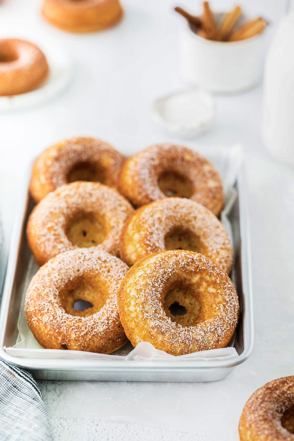 closeup of several baked donuts on a small silver tray