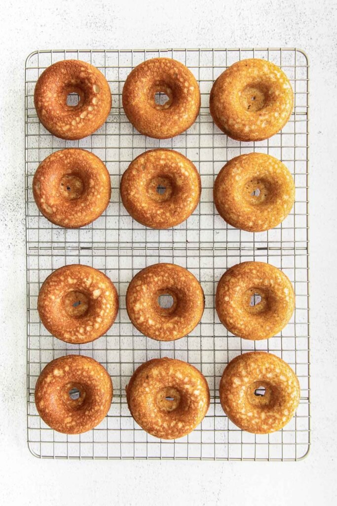 twelve baked donuts on a wire rack