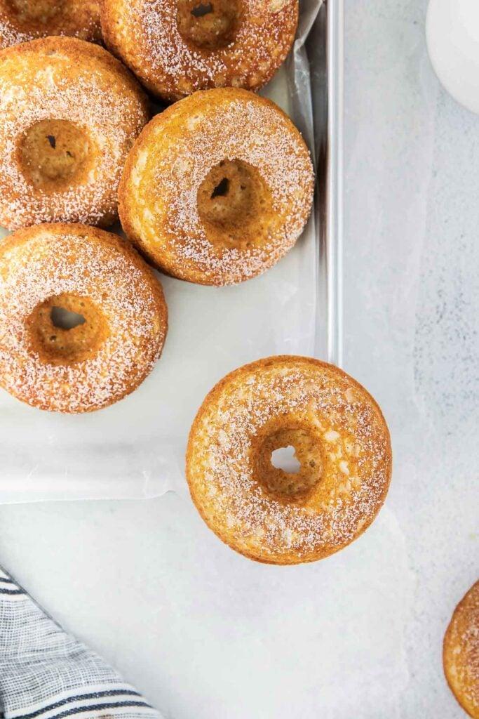 closeup of baked donuts on a baking sheet