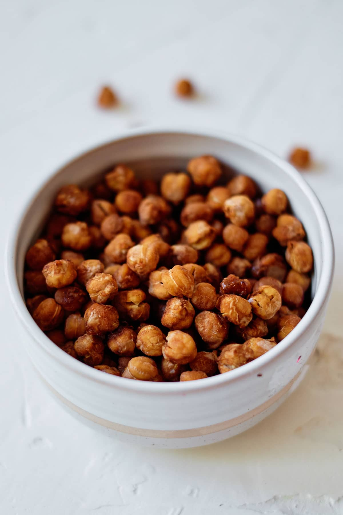 closeup of a white bowlful of pumpkin spice roasted chickpeas