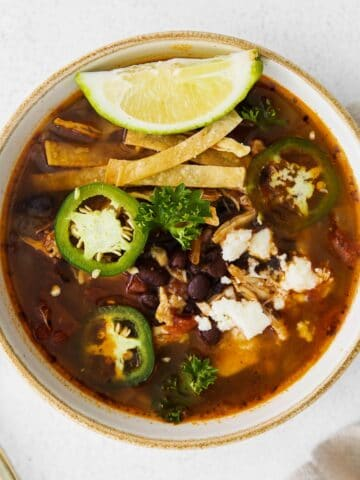 closeup of a white bowl of soup with chicken, black beans, tortilla strips and sliced jalapenos