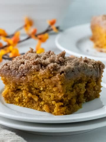 closeup of a slice of pumpkin coffee cake with crumb topping in a white plate