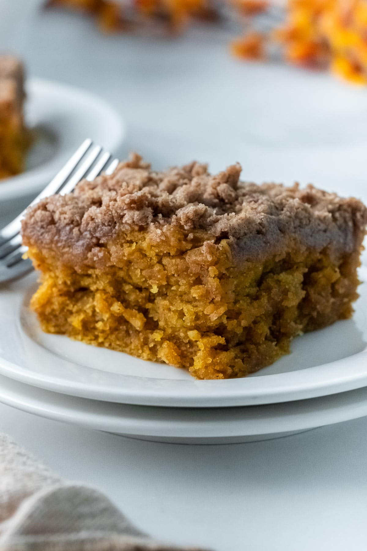slice of pumpkin coffee cake with buttery crumb topping on a white plate with a fork
