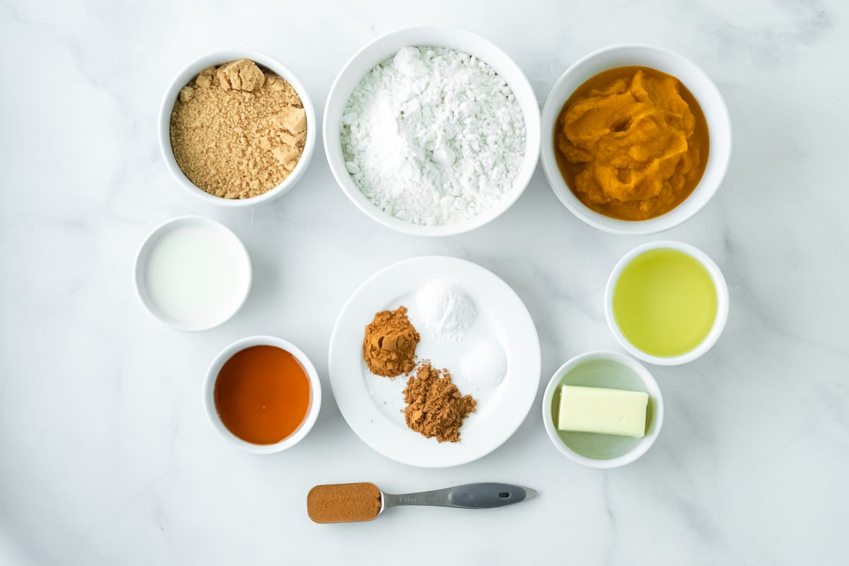 several small white bowls with ingredients for pumpkin coffee cake - flour, butter, brown sugar, oil, maple syrup, milk and spices