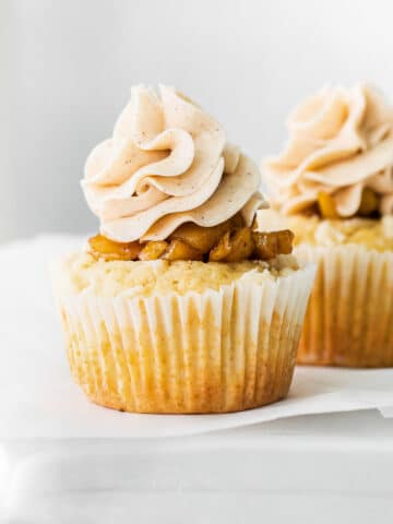 closeup of a vanilla cupcake topped with diced apple pie filling and buttercream frosting