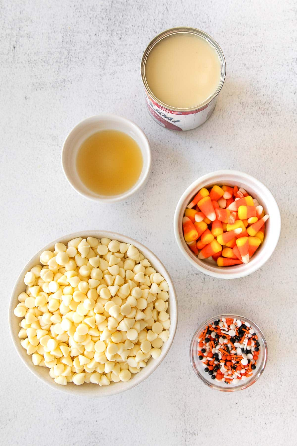 several bowls filled with white chocolate chips, halloween sprinkles, candy corn, vanilla extract and a can of condensed milk