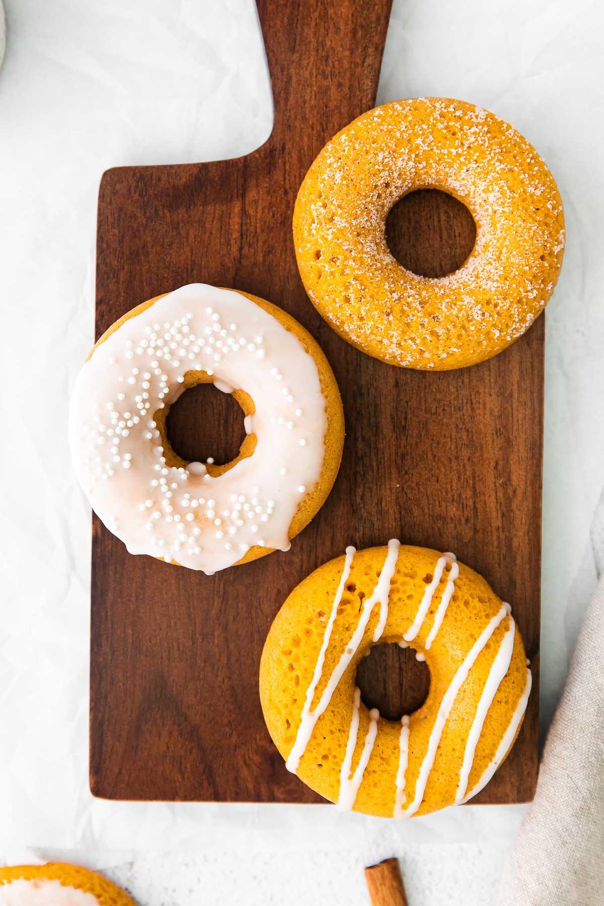 three glazed and drizzles pumpkin donuts on a dark wood board