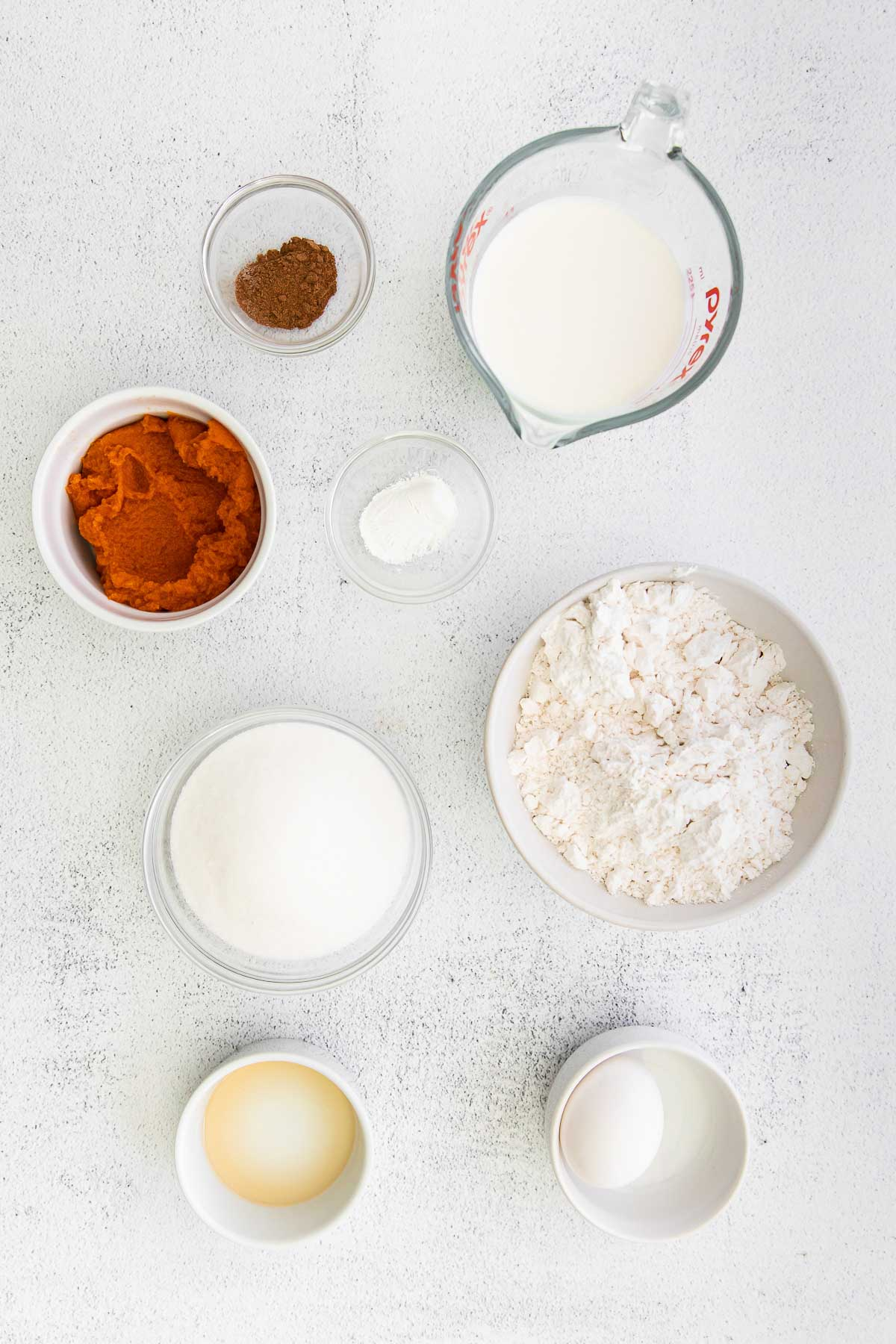 several small white bowls with ingredients for pumpkin donuts - flour, pumpkin puree, sugar, vanilla, milk and spices